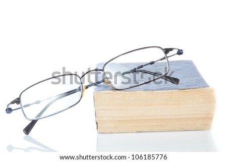 The book is a dictionary and glasses on a white background.