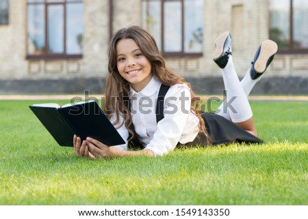 The book is genius. Genius bookworm relax reading on green grass. Happy little genius read book outdoor. Small wunderkind. Child prodigy. Back to genius school.