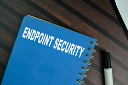 The book of Endpoint Security isolated on Wooden Table.