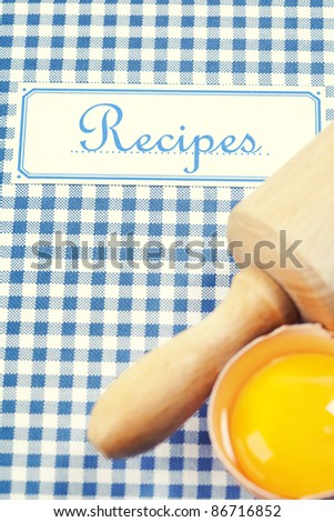 The book of recipes with egg and rolling pin