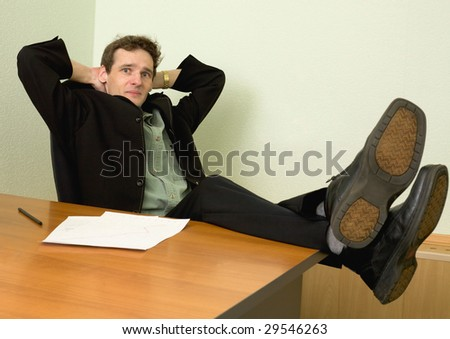 The boss in black suit on a workplace - stock photo