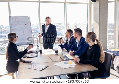 The boss stands near the board with graphs, demonstrates statistics, various personnel attending the training, introduces the new products of the company, reports on the results of work for partners.
