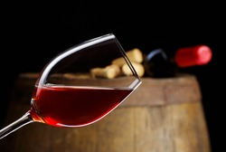 The bottle of red wine and glass and barrel