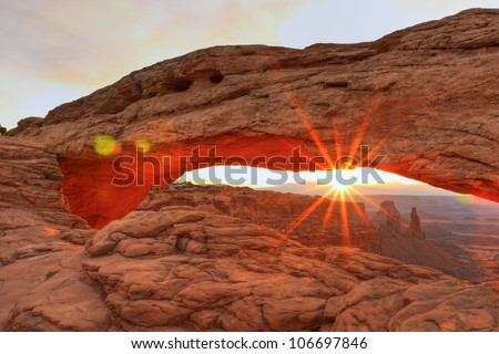 The bottom of Mesa Arch glows red at Sunrise as the sun flares over the mountains in Canyonlands National Park in Utah