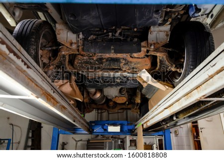 The bottom of the car lifted on a lift covered with brown and orange rust during anti-corrosion treatment. Auto service industry.