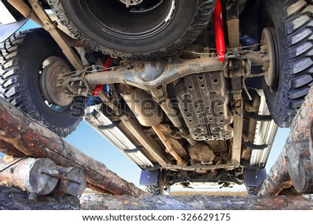 The bottom of the jeep, car bottom, off-road vehicle, car on the country road, a prestigious transport, horizontal image, jeep standing on the logs, inspection jeep below, car against the sky. #326629175