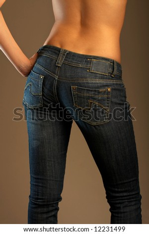 The bottom part of a female body dressed in jeans and turned by back