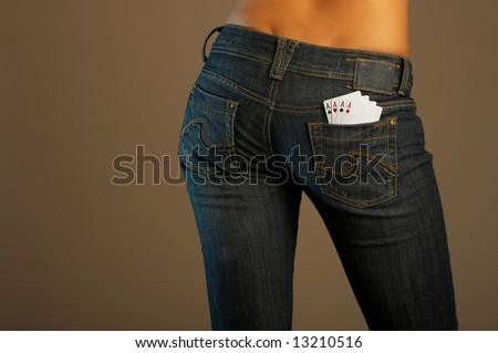 The bottom part of the girl in jeans with four cards in a pocket