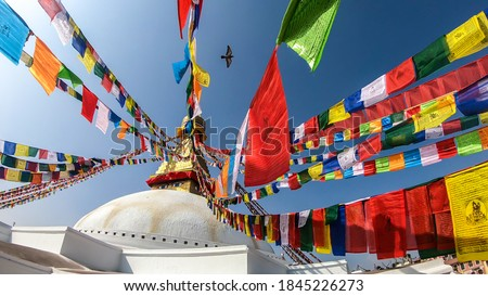 The Bouddhanath Temple in Kathmandu, Nepal. The temple has many colourful prayer flags with 'om mani padme hum' mantra written on them attached to it's golden rooftop. Spirituality and meditation. Photo stock ©