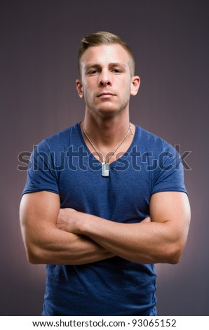 The bouncer, portrait of tough looking muscular young man, arms folded.