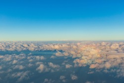 The boundaries of the Earth's atmosphere between the troposphere and the stratosphere show clouds that are at the top of the troposphere and the blue sky.