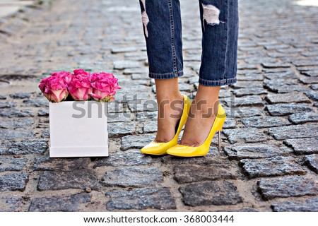 The bouquet of pink roses and female legs in jeans and yellow shoes with heels.  #368003444