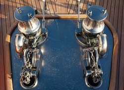 The bow of a luxury yacht with stainless steel winches, anchor chains and teak deck, top view.