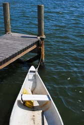The bow of a small rubber dingy boat or rowboats near a wharf. The boat is white in color. The pier is a small wooden pier surrounded by a pond of blue water. The boat is tied to a wooden post.
