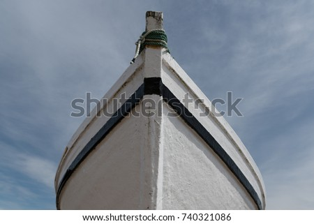 The bow of a white boat with black trim and green rope.  There's a blue sky with soft clouds in the background. #740321086