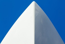 The bow of a white yacht against a blue sky. View from below.