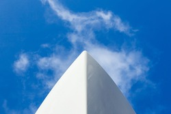 The bow of a white yacht, against a blue sky with white clouds. View from below.