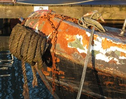 The bow of an old rusty iron canal boat moored with ropes on a jetty with reflections in dark water