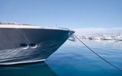 The bow of big yacht moored at marina.