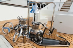 The bow of the yacht with teak deck, with anchor stops, part of the anchor chain, winch for tightening and ship bell made of stainless steel.