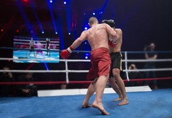 the boxer in the ring strikes the opponent in the arena of full light