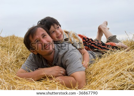 The boy and father on golden hay