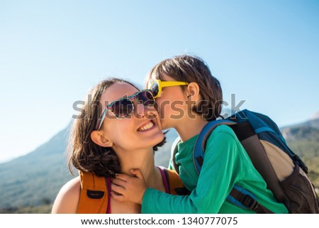 The boy and his mother are sitting on the top of the mountain. A woman travels with a child. Baby kisses and hugs mom. Travel with backpacks. Hike and climb with kids. Portrait of a woman and her son. #1340777075
