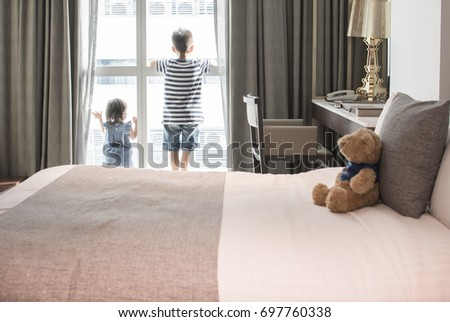 The boy and little girl were waiting for something by the window in the bedroom.