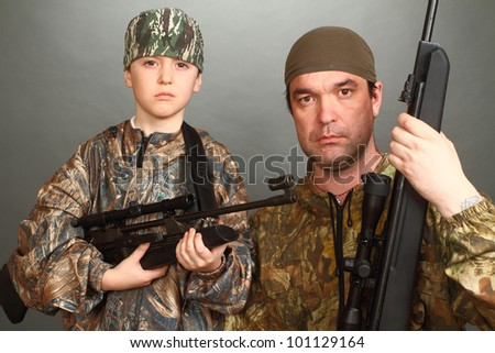 the boy and the adult man in a camouflage with rifles nearby in a shot, look in the chamber, a close up