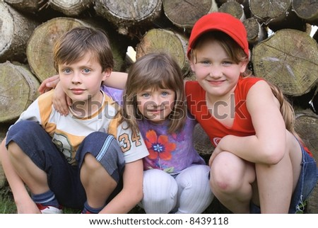 The boy and two girls sitting in the cheap with others.