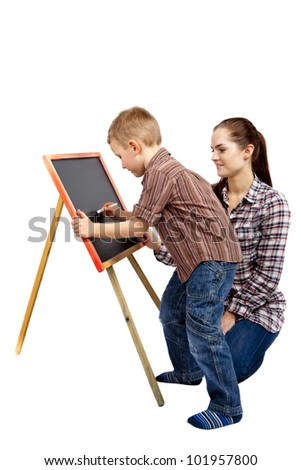 The boy begins to write on the blackboard. He wants to draw or write something. The woman is  watching what he does.