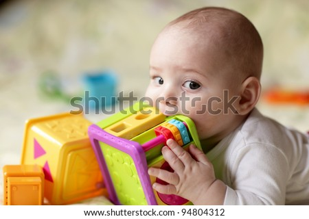 The boy biting a toy on a bed at home