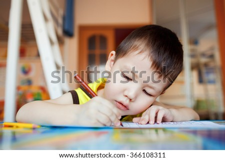 The boy carefully and intently draws in a special notebook for drawing, education at home, pre-school training, the development of creative abilities of children. Classroom in the house.