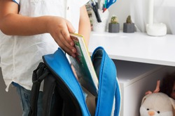 The boy collects a school backpack, folds notebooks and books. Preparing for school concept. Going ready to school