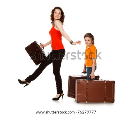The boy drags the big suitcase after the graceful woman