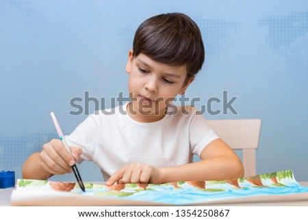 The boy draws with colorful paints drawing. The child is passionate about creativity. Additional education student. Artistic interest. The young artist expresses his attitude to the world. #1354250867
