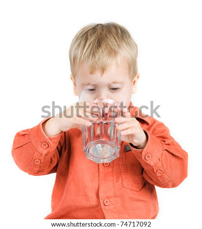 The boy drinks water from a glass