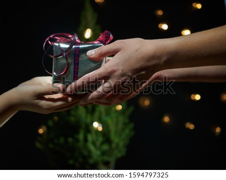 The boy gives mom a gift for Christmas, close up view