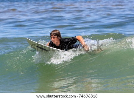 The boy goes for a drive on a surfboard