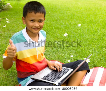 The boy happy with notebook on green grass at backyard