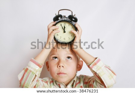 The boy holds an alarm clock on a head.