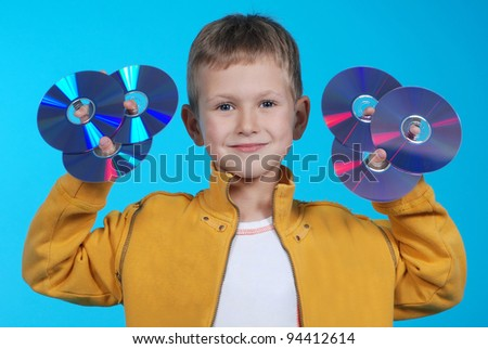 The boy holds six CD or DVD