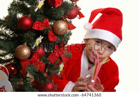 The boy in a suit of Santa Claus drinks Coca-Cola through a straw