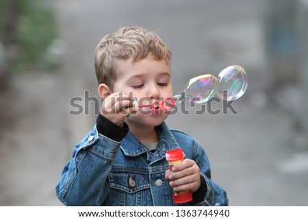 The boy in the denim jacket blows bubbles #1363744940
