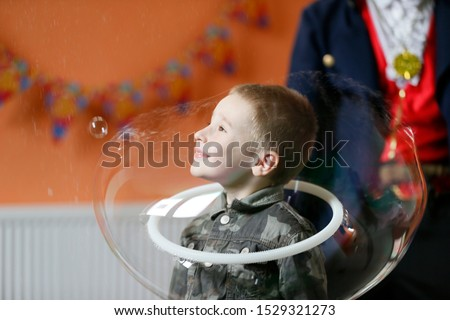 The boy in the soap bubble. Child have fun at the party.