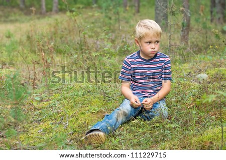 The boy in the woods sitting on moss.