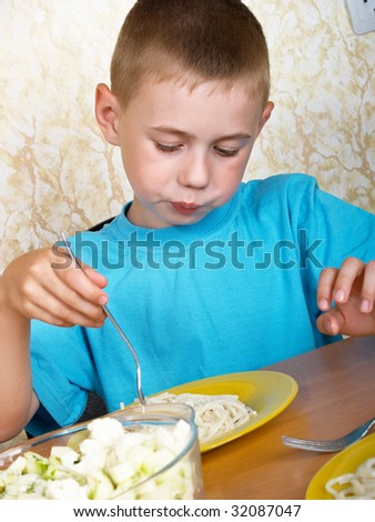 The boy is a spaghetti behind a table