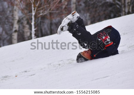 The boy is rolling down mountain in winter on his back. Child falls from snow slide. Boy tumbles off hill in snow. Child rolls upside down on ground in winter. Funny children's winter games. Stockfoto ©