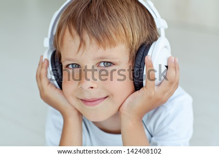 The boy is smiling  and listening to music