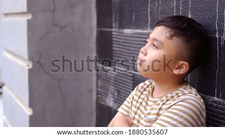 The boy is thinking and leaning against the wall and looking up